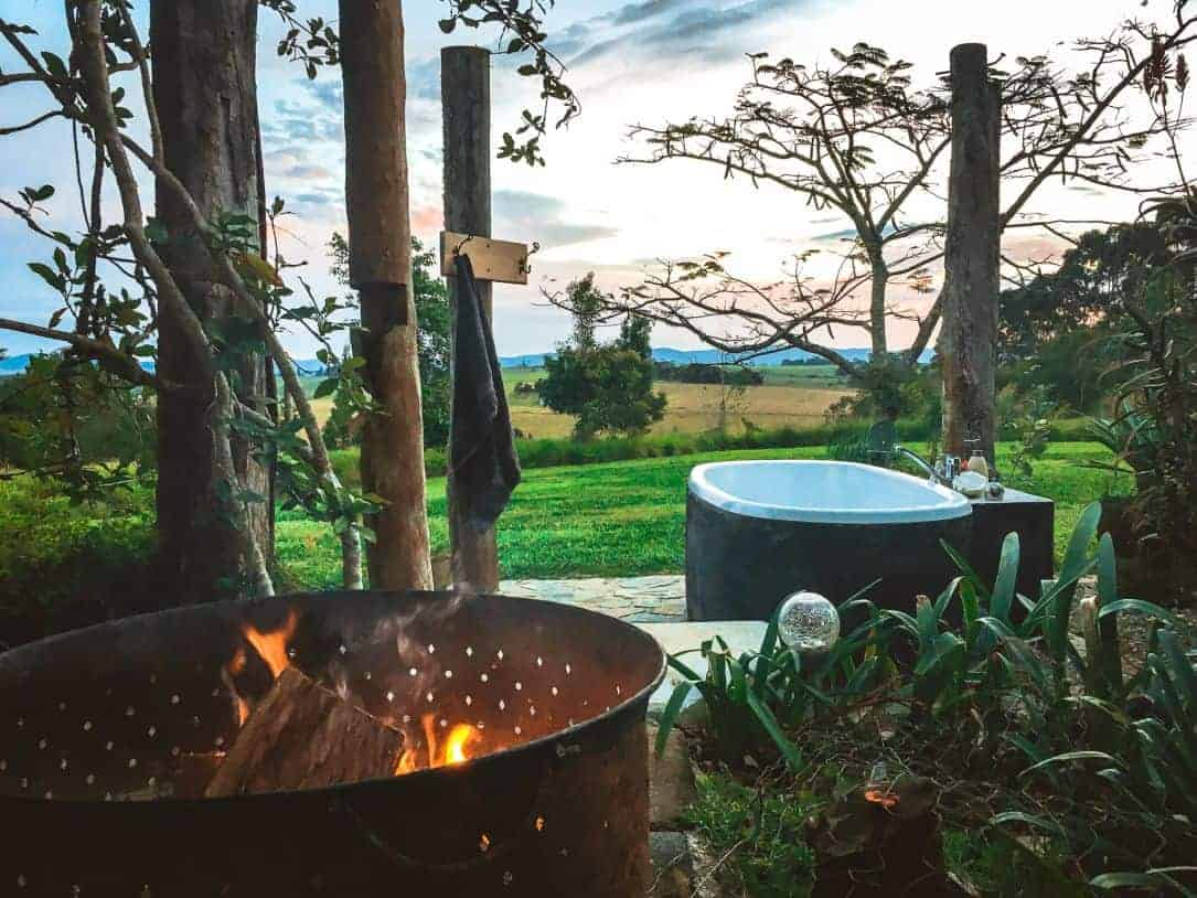 Airbnb accommodation 'Hemingway's on the Hill' in Peeramon, Qld. A beautiful outdoor fireplace and bathtub with a view.
